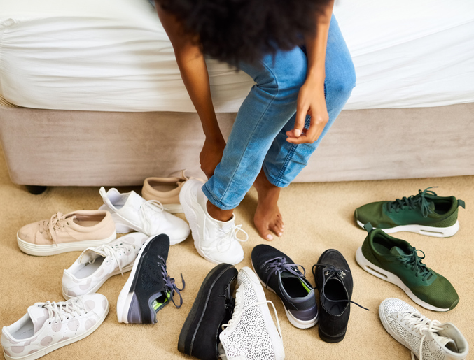 Cropped shot of a woman trying on different pairs of shoes